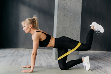 fitness woman doing leg exercises with yellow fitness gum