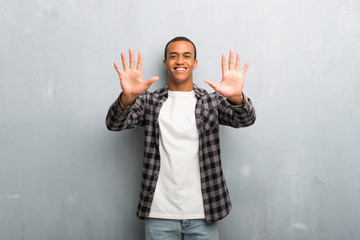 Young african american man with checkered shirt counting ten with fingers