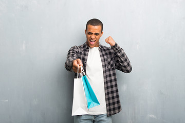 Young african american man with checkered shirt holding a lot of shopping bags