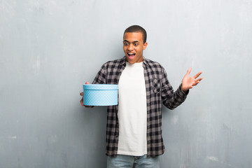 Young african american man with checkered shirt surprised because has been given a gift