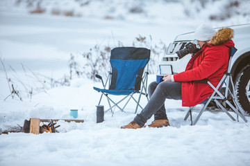 young adult man sitting in chair near winter camp fire taking picture on camera