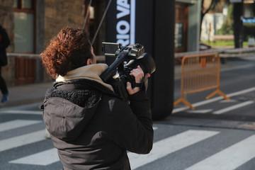 Mujer de mediana edad de espaldas sujetando cámara de vídeo o televisión en evento deportivo