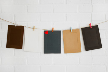 Blank paper frames on white brick wall