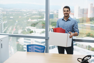 Successful Confident Businessman Moving To New Office Looking At Camera