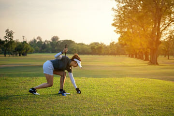 Sporty asian golfer woman putting golf ball on tee with club in golf course on sunny day for healthy sport. Lifestyle and Sport Concept