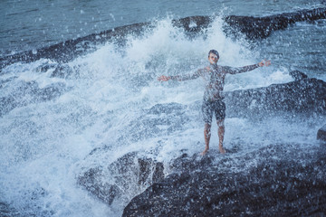 A tattooed man lies on the edge of a cliff. splashes of ocean waves.