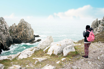 woman tourist taking photos with her smartphone at the cape of Pen Hir on the Crozon peninsula in France .