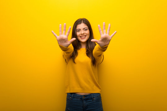 Teenager girl on vibrant yellow background counting ten with fingers