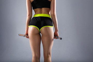 Buttocks of a beautiful young unidentified sports woman with dumbbells in her arms in a sport suit. Concept of a beautiful figure and strength training