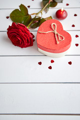 Single fresh red rose flower on the white wooden table with heart shaped sequins sprinkled around, candles and gift in box. Valentines or love concept. With copy space.