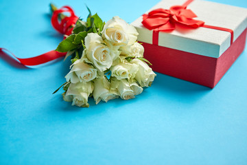 Bouquet of white roses with red bow on blue background. Boxed gift on side. Valentine or love concept image. Floral background image with copy space for text