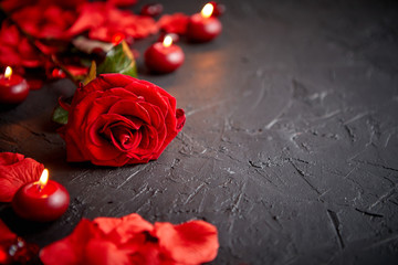 Love and Valentines day concept. Red rose, petals, candles, dating accessories, boxed gifts, hearts, sequins on black stone background, frame composition, top view. Layout for greeting card