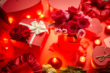 Valentines day romantic decoration with roses, boxed gifts, candles, on a red background table. Top view, copy space.