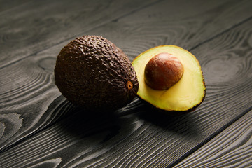 Image of avocado on black wooden background