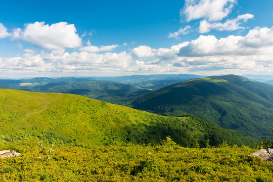 beautiful landscape of carpathian mountains. grassy alpine meadows, deep valleys and distant forested hills. wonderful sunny weather at sunset in summertime. fluffy clouds on the blue sky
