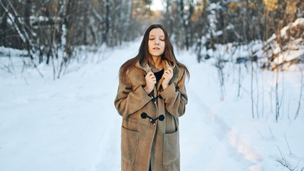 Brown-haired in a robe walks through the winter forest. Freshness and lightness.
