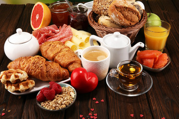 breakfast on table with bread buns, croissants, coffe and juice on valentines day.