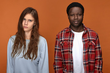 Young interracial couple having relationships troubles. Grumpy black male and his white wife quarreling, not speaking to each other, standing against blank studio wall background, frowning
