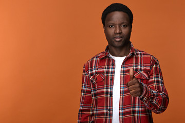 Portrait of stylish trendy looking young Afro American man in his twenties posing against blank studio background with thumbs up gesture, expressing approval, satisfaction and positive attitude