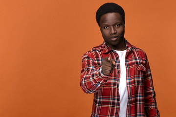 We choose you. Stylish attractive young Afro American man in plaid shirt having serious confident facial expression, pointing index finger at camera posing against blank orange studio wall background