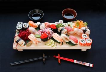 Aluminium Prints Sushi bar Assorted types of sushi on bamboo table with hashi chopsticks and shoyu. Sushi on black background.