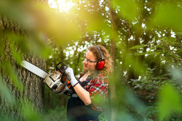 Shot of professional lumberjack in the forest cutting an oak trunk with chainsaw.