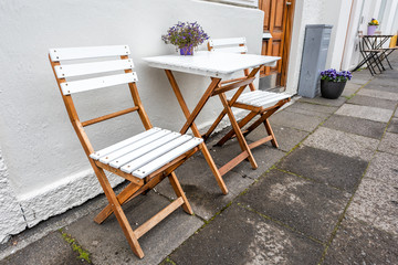 White empty wooden table outside restaurant cafe with two chairs on sidewalk street and purple flowers in flowerpot potted plant setting with nobody in Iceland