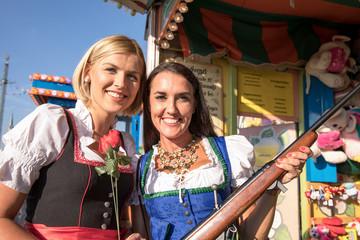 2 junge sexy Frauen haben Spass auf dem Frühlingsfest, Oktoberfest, Wiesn, mit Lebkuchenherz Schokobane vor dem Riesenrad Luftballons