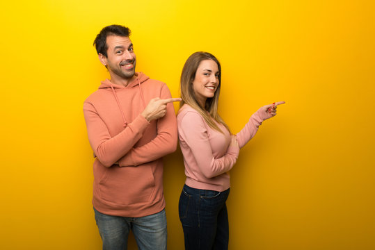 Group of two people on yellow background pointing finger to the side in lateral position