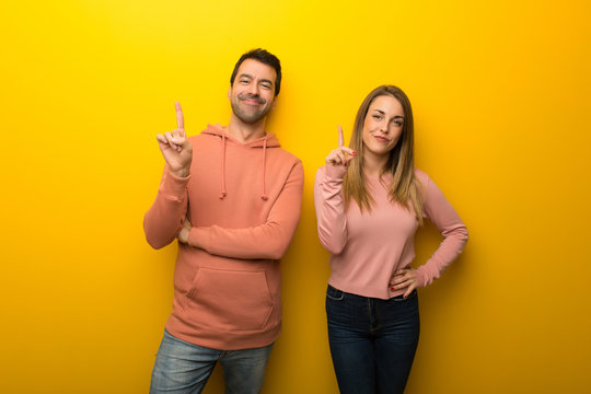 Group of two people on yellow background showing and lifting a finger in sign of the best
