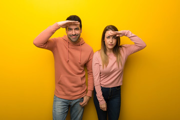 Group of two people on yellow background looking far away with hand to look something Wall mural