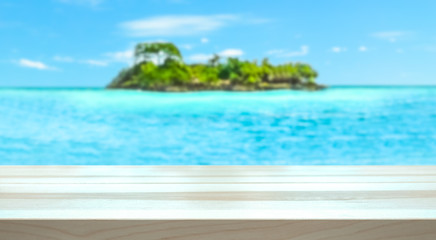 Empty table top for product display montage. Tropical holiday concept. Paradise island and ocean blurred in the background.