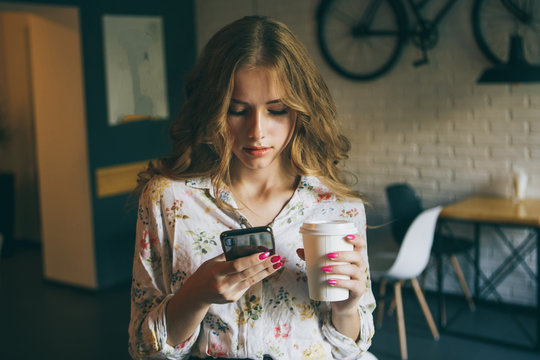 Picture of young cute blonde girl with a cup of coffee holding phone and typing text, beautiful yong woman with bright pink nails concentrate her black mobile