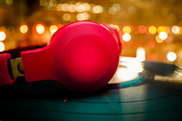 Headphones on a blue vinyl record with bright lights in the background at night
