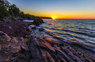 Rocky Coastal Sunset Landscape. Sunset over the horizon of Lake Superior with a rocky coastline in the foreground. Copper Harbor, Michigan, USA.