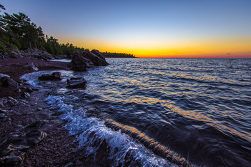 Lake Superior Twilight Beach. Beautiful sunset colors on a remote rocky beach on the coast of Lake Superior in Copper Harbor, Michigan.