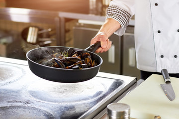 Frying shell mussels in pan. Chef frying oven-steamed mussles in pan on stove.