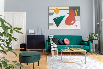 Luxury and modern home interior with green velvet design sofa, coffee tables , commode and pouf. Tropical plant in grey stand. Grey walls with abstract painting. Stylish decor of living room.
