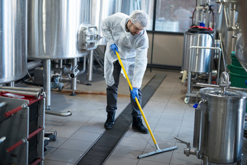 Industrial cleaning service. Industrial worker cleaning production plant floor.