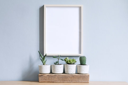 Minimalistic home interior with mock up photo frame on the brown table with composition of cacti and succulents on the wooden piece in stylish cement pots. Grey walls. Stylish concept of home garden.