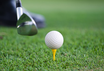 Close-up view of a golf ball set on a wooden golf tee in the grass with a golf club positioned behind it as though about to hit the ball
