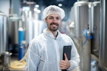 Fototapeta Portrait of smiling technologist in industrial plant. obraz
