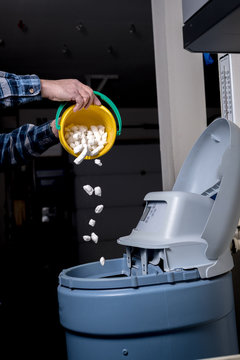 Man pours fresh salt from a yellow bucket into a water softener