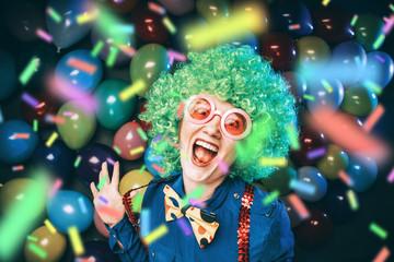 Frau in Karnevalstimmung auf einem bunten Hintergrund aus Luftballons