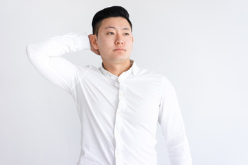 Relaxed Asian man holding hand behind head. Young guy having break and looking away. Relaxed man concept. Isolated front view on white background.