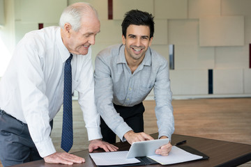 Cheerful entrepreneur showing application to colleague. Smiling businessmen discussing information on tablet computer at meeting. Successful work concept
