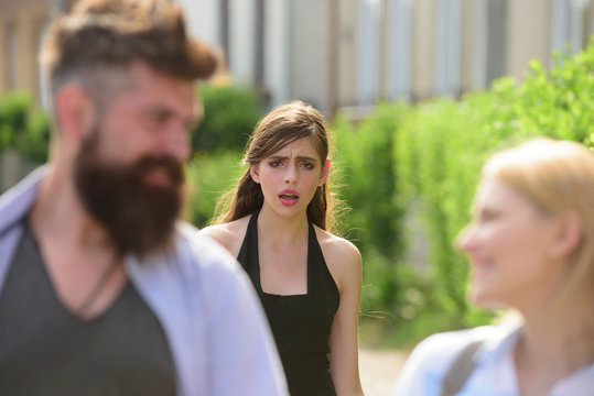 Very jealous and insecure. Unhappy girl feeling jealous. Jealous woman look at couple in love on street. Romantic couple of man and woman dating. Bearded man cheating his woman with another girl