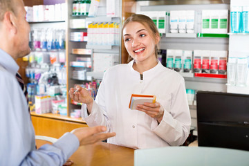 Smiling  female pharmacist counseling customer about drugs usage