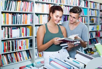 portrait of  teenage girl customer looking at open book standing among bookshelves