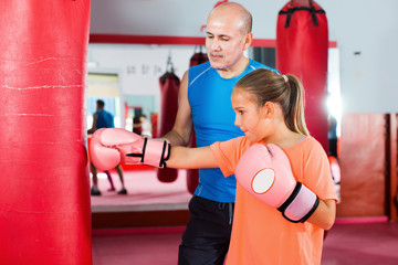 Young girl at boxing workout on punching bag